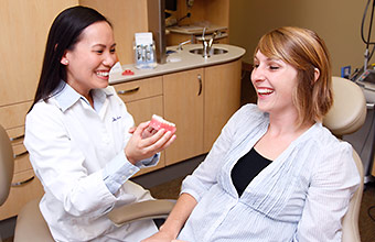 Dentist reviewing Invisalign sample with patient